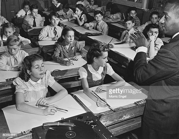 An unidentified black teacher plays music from a record player as he leads a class of white students who listen from their desks with paint brushes...