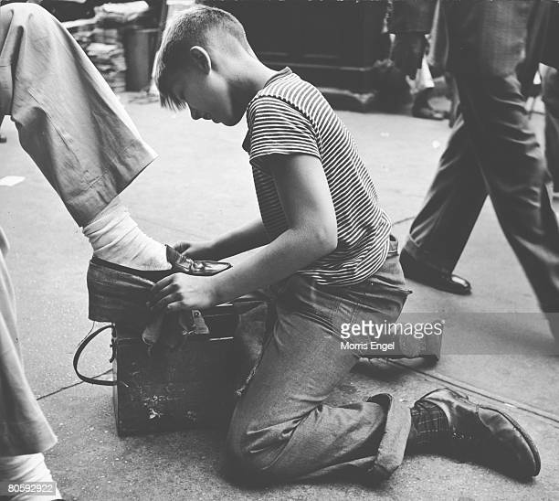 An unidentified boy kneels on the sidewalk as he shines shoes on 14th Street New York New York mid to late 1940s