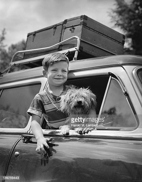 An unidentified boy leans out of the open window of a car a dog by his side 1956 There are several trunks on the car's luggage rack