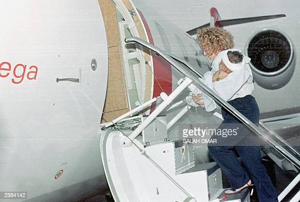 An unidentified British nurse carries the Sudanese boy who emerged as the sole survivor of a plane crash earlier this week into a chartered Swiss...