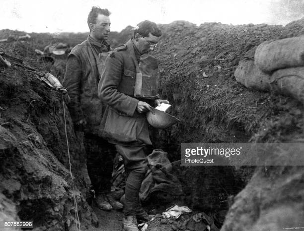 An unidentified chaplain of the Royal Munster Fusiliers says a prayer over the bodies of two soldiers in a British front line trench during the last...