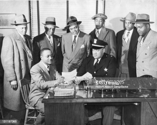 An unidentified Chicago police officer shows a series of documents to American newspaper publisher John H Sengstacke as a group of men stand behind...