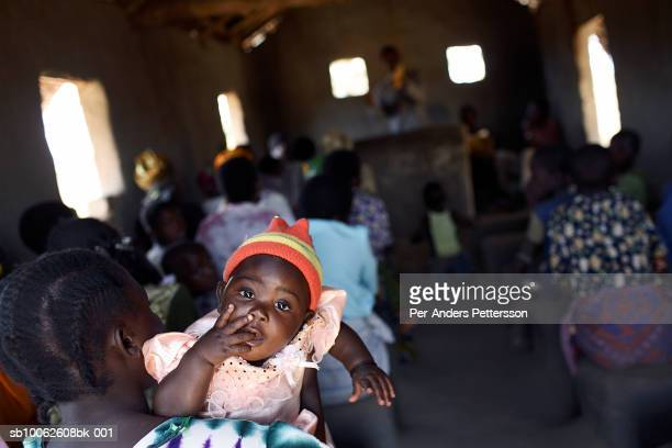 An unidentified child with her mother during a church service at the African Abraham Church on August 20 2006 in Mphandula village about 30 miles...