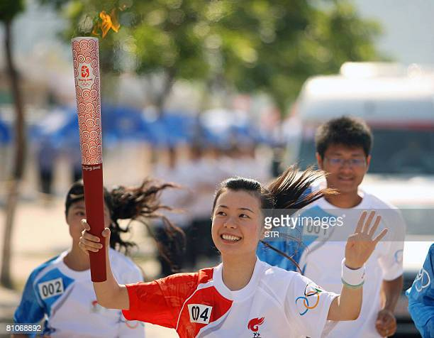 An unidentified Chinese torch bearer carries the 2008 Beijing Olympic Games flame as the torch relay arrives in Quanzhou southeast China's Fujian...