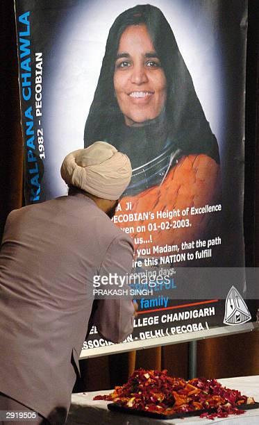 An unidentified classmate of Indianborn astronaut Kalpana Chawla offers a floral tribute in front of a poster on the first anniversary of her death...