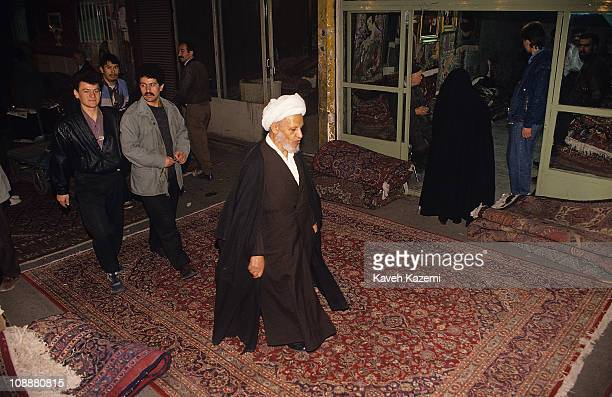 An unidentified clergyman in a white turban walks on a Persian carpet laid on the floor outside a shop at a bazaar, Tehran, Iran, December 11, 1995.
