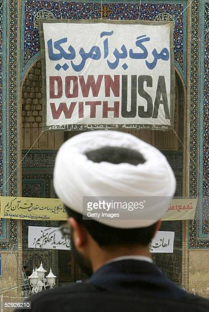"""An unidentified clergyman stands facing a sign which reads, """"Down With USA"""" as he attends a protest gathering at the Faizieh religious school May 18,..."""