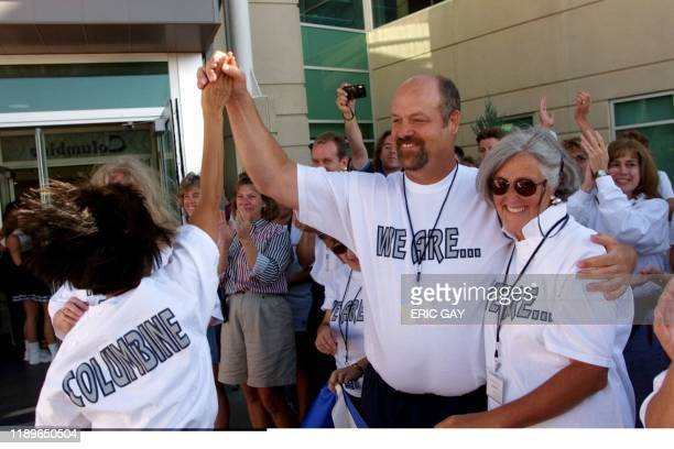 An unidentified Columbine High School student exchanges a high five with an unidentified Columbine teacher 16 August 1999 as she walks into the...