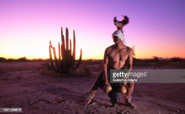 An unidentified, costumed man performs a Deer Dance as the sun sets behind him, Tamaulipas, Mexico, 1978.