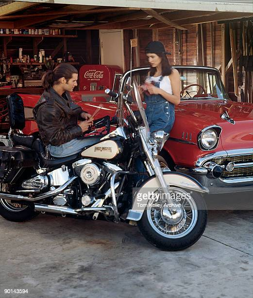 An unidentified couple examine tools in a garage the leatherjacket and jeans wearing longhaired man seated on a HarleyDavidson FLSTC Heritage Softail...