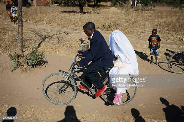 An unidentified couple rides on a bicycle home from their wedding on August 19 2006 in Mphandula village about 30 miles outside Lilongwe Malawi...