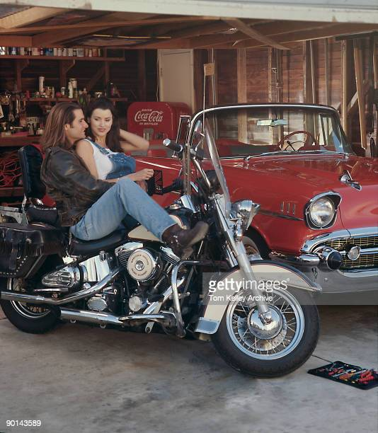 An unidentified couple smile at each other as the leatherjacket and jeans wearing longhaired man sits back on a HarleyDavidson FLSTC Heritage Softail...