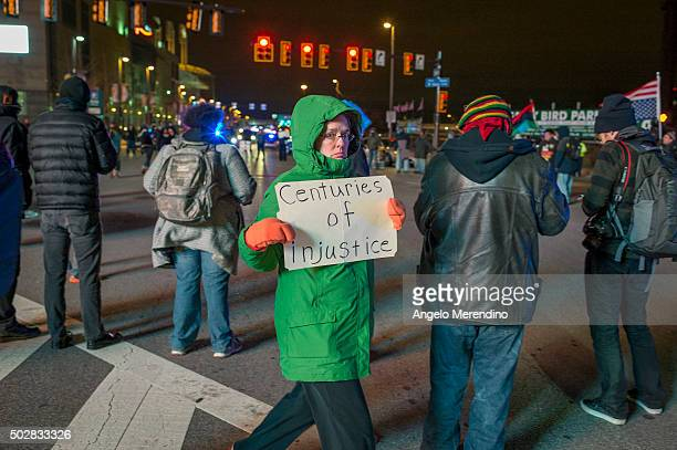 An unidentified demonstrator carries a sign at the intersection of Ontario Street and Huron Road near Quicken Loans Arena on December 29 2015 in...