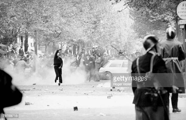 An unidentified demonstrator in black steps from the crowd and smoke to hurl something at uniformed officers in the foreground during riots on...
