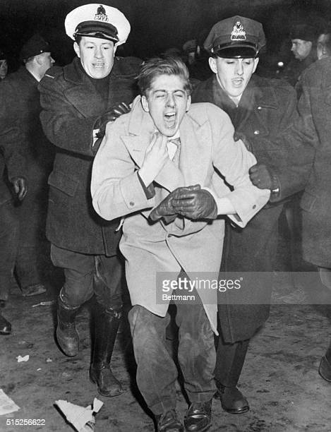 An unidentified demonstrator is taken into custody by constables Charles Hynes and Jacques Belanger outside the Montreal Forum during a riot...