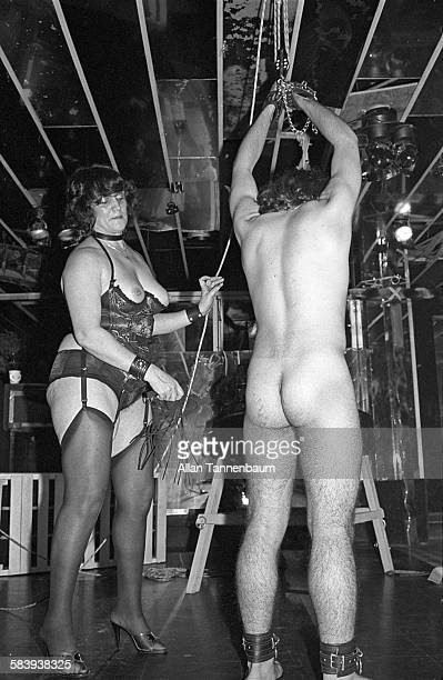 An unidentified dominatrix whips man during an SM show at the Plato's Retreat swinger's club New York New York July 14 1980