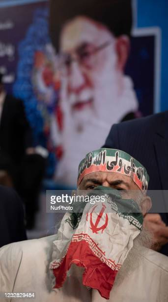 An unidentified elderly man covers his face with an Iran flag instead of protective face mask looks on while attending under a portrait of Irans...
