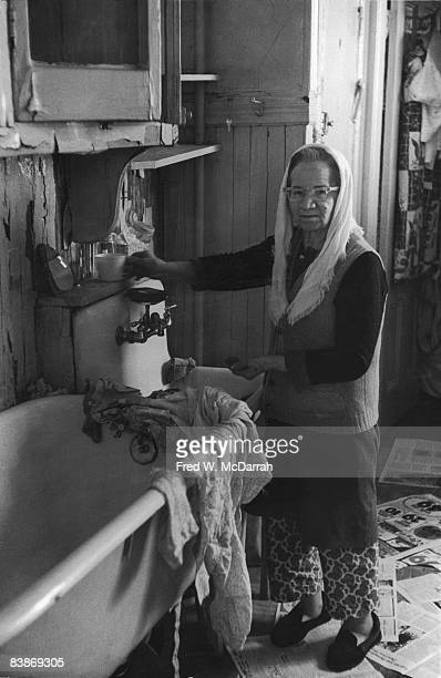 An unidentified elderly woman stands at a sink next to a bathtub in her tenement apartment's kitchen New York New York February 18 1971 Newspapers...