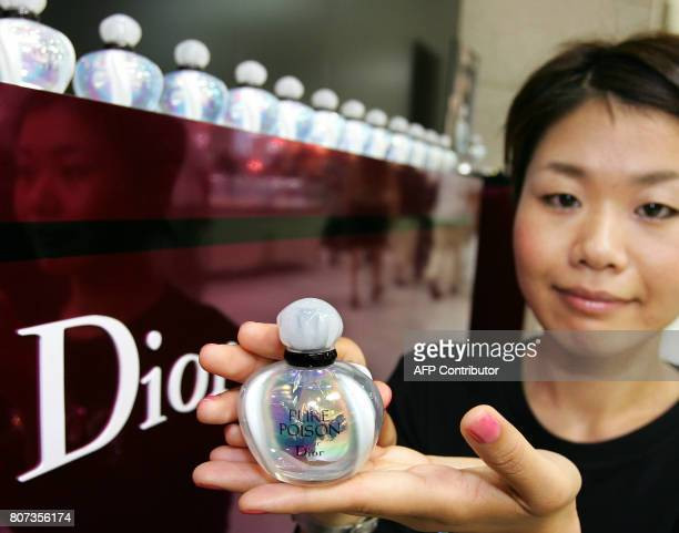 """An unidentified employee of French cosmetics giant Christian Dior displays a sample of """"Pure Poison"""" perfume during its promotional sales at Tokyo's..."""