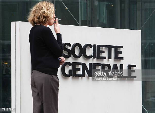 An unidentified employee of the Societe Generale Bank smokes a cigarette outside the bank's headquarters on January 24 2008 in La Defense Fraud by a...