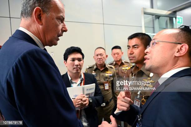 An unidentified employee of the United Nations High Commissioner for Refugees talks with Thai immigration officers at the Suvarnabhumi international...
