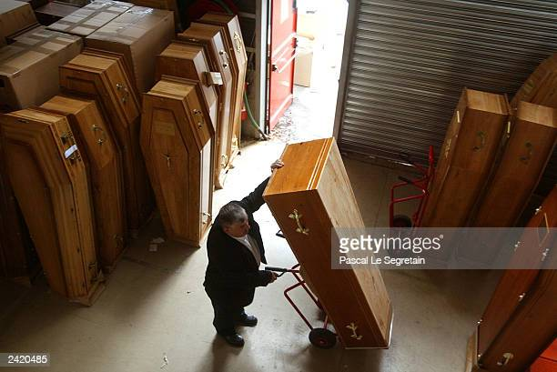 An unidentified employee puts places an empty coffin at an undertaking company August 23 2003 in Aubervilliers France Morgues are overflowing with...