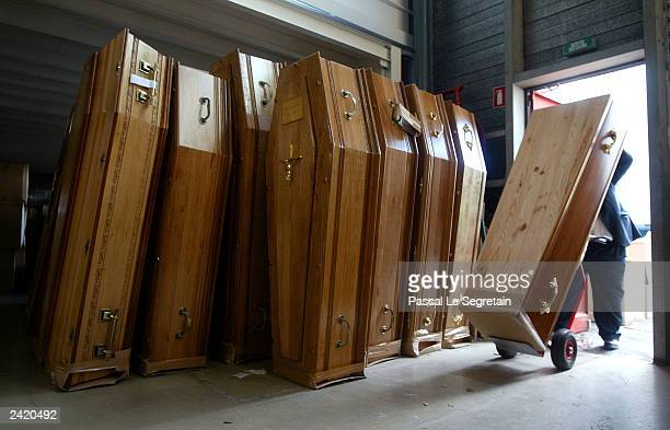 An unidentified employee puts places an empty coffin at undertaking company August 23 2003 in Aubervilliers France Morgues are overflowing with...