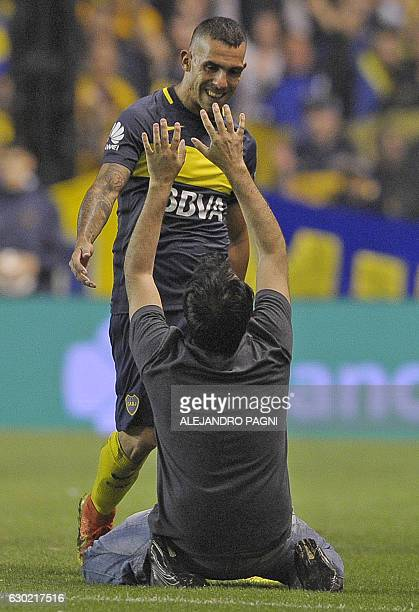 An unidentified fan cheers Boca Juniors' forward Carlos Tevez as he leaves the field during their Argentina First Division football match against...