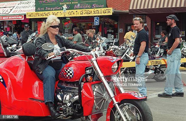 An unidentified female biker rolls down main street during the 61st annual motorcycle rally held 0612 August 2001 in Sturgis South Dakota Thousands...