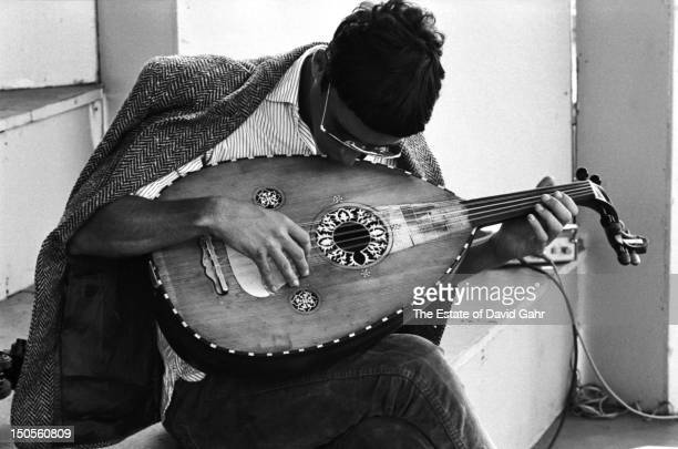 An unidentified folk musician plays an oud a Middle Eastern stringed instrument backstage at the Newport Folk Festival in July 1964 in Newport Rhode...