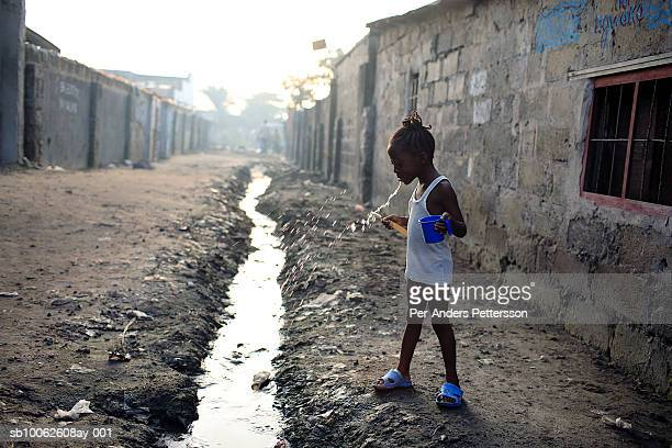 An unidentified girl brushes her teeth outside her house on April 23 2006 in central Kinshasa Congo DRC The area one of the poorest in the capital is...
