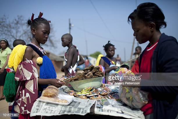 An unidentified girl buys dried fish from a trader before a traditional Reed dance ceremony at the Royal Palace on August 30 in Ludzidzini Swaziland...
