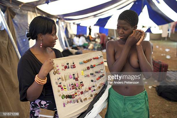 An unidentified girl buys earrings from a trader before a traditional Reed dance ceremony at the Royal Palace on August 29 in Ludzidzini Swaziland...