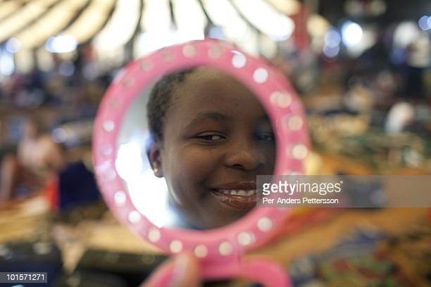 An unidentified girl checks herself in a mirror before a traditional Reed dance ceremony at the Royal Palace on August 29 in Ludzidzini Swaziland...