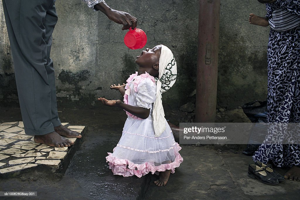An unidentified girl drinks holy water at -Ebale Mbonge+ on April 23, 2006 in central Kinshasa, Congo, DRC. It+s a spiritual place where members come to get cured from bad and evil spirits. Many are suffering from different diseases and they hope to get cured while getting treatment. Kinshasa, a city of about eight million people is battling with bad infrastructure and no public transport. Congo, DRC is in ruins after forty years of mismanagement by the corrupt dictator and former president Mobuto Sese Seko. He fled the country in 1997 and a civil war started. The country is planning to hold general elections by July 2006, the first democratic elections in forty years.,