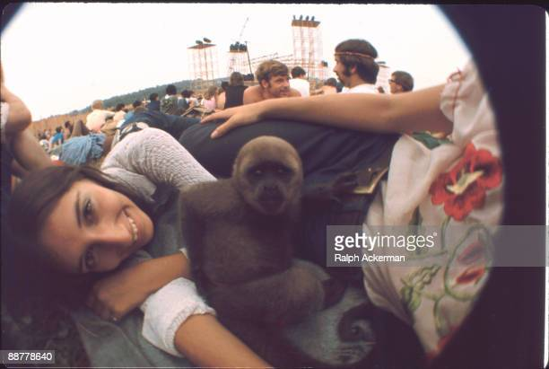 An unidentified girl smiles while her pet monkey sits in the middle of her group at the Woodstock Music Festival Bethel NY August 1969