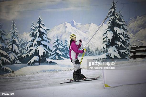 An unidentified girl uses a ski lift in an indoor ski resort at the Windows Of the World Theme park on September 28 2008 in central Shenzhen China...