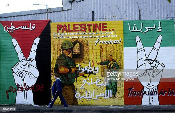 An unidentified girl walks past a portion of a mural on Falls Road August 20, 2002 in west Belfast, Northern Ireland. The pro-Palestinian painting...