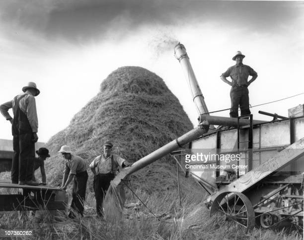 An unidentified group of farmers operate a threshing machine mid twentieth century