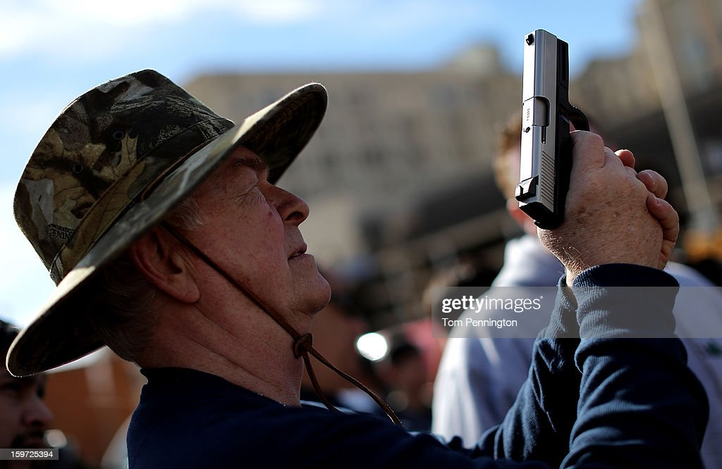 An unidentified gun enthusiast inspects an unloaded pistol that was being sold in an impromptu auction across the street from a gun buy back program at the First Presbyterian Church of Dallas on January 19, 2013 in Dallas, Texas. U.S. President Barack Obama recently unveiled a package of gun control proposals that include universal background checks and bans on assault weapons and high-capacity magazines.