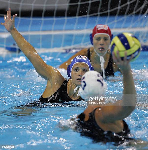 An unidentified Hungarian player helps goalkeeper Patricia Horvath protect the goal from Canada's Johanne Begin during their women's water polo...