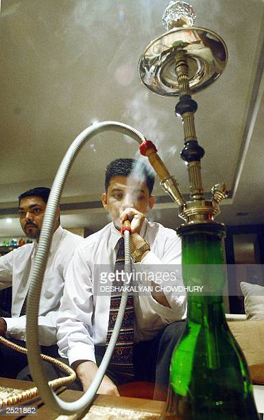 An unidentified Indian man puffs away at a 'Hookah' at a newly opened Hookah Bar at the Grain of Salt restaurant in Calcutta, 21 September 2003. The...