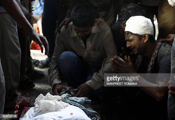 An unidentified Indian man weeps beside the body of a relative who died in one of the New Delhi bomb blasts, at a crematorium in New Delhi on...