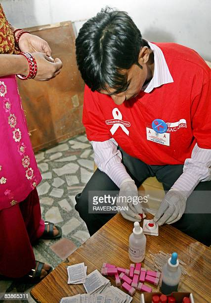 An unidentified Indian volunteer tests blood for HIV as part of a programme of testing on World Aids Day in New Delhi on December 1 on of World AIDS...