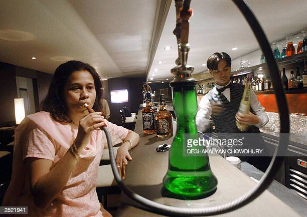 An unidentified Indian woman puffs away at a 'Hookah' as a bartender works behind the bar at a newly opened Hookah Bar at the Grain of Salt...