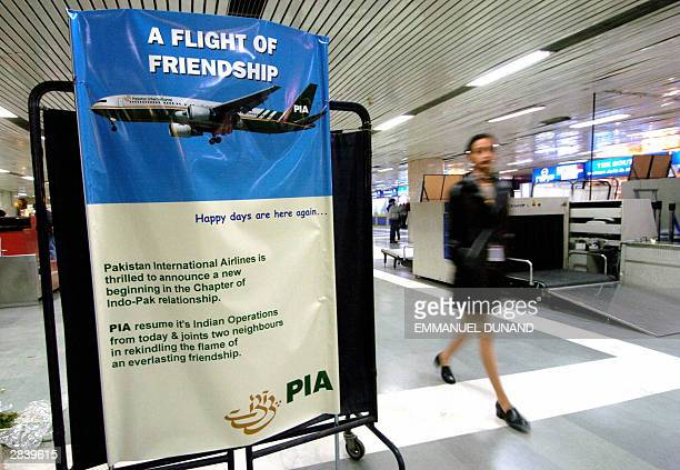 An unidentified Indian woman walks past a poster for Pakistan International Airlines flight resumption between India and Pakistan 01 January 2004 at...