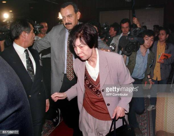 An unidentified Japanese woman a relative to a victim of the Luxor massacre is escorted past journalists and cameramen at the Cairo airport 19...