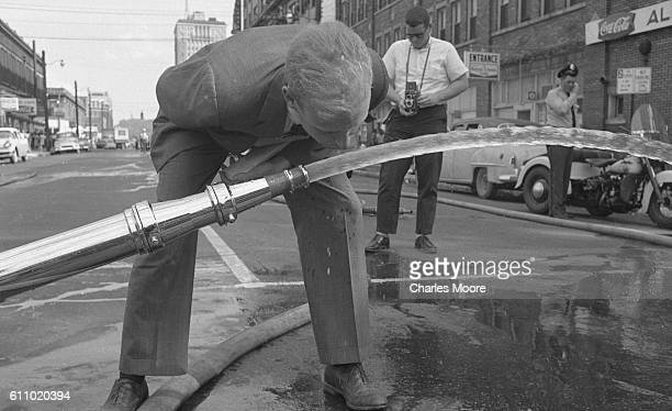 An unidentified journalist bends down to drink from a firehose on 17th Street North near Kelly Ingram Park Birmingham Alabama early May 1963 Police...
