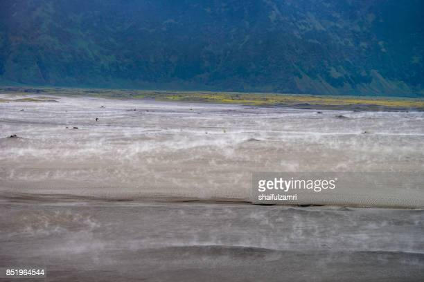 an unidentified local walking in sandstorm near mount batok at bromo tengger semeru national park, east java, indonesia on march, 2 2014. - shaifulzamri stock pictures, royalty-free photos & images