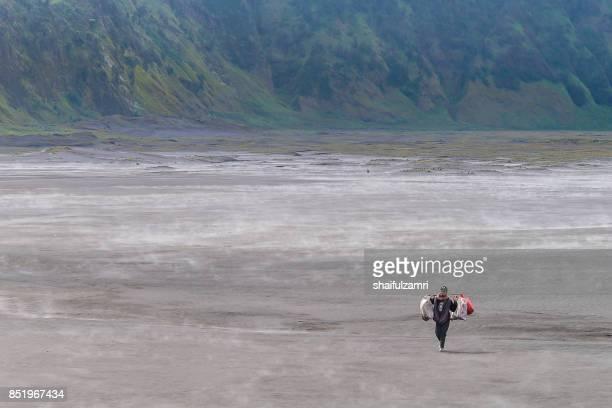 an unidentified local walking in sandstorm near mount batok at bromo tengger semeru national park - mt semeru stock pictures, royalty-free photos & images